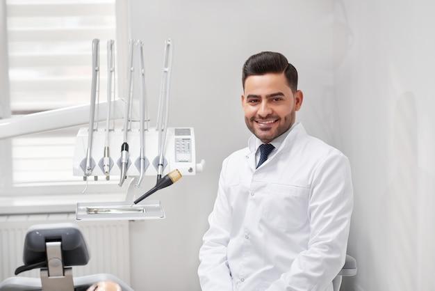 Jonge vrolijke mannelijke professionele tandarts glimlachend vreugdevol zittend op zijn kantoor