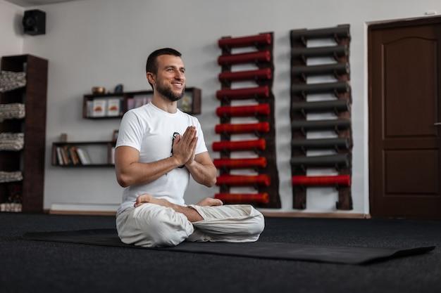 Jonge vrolijke mannelijke trainer met een positieve glimlach zit in de lotuspositie in de sportkamer. professionele man die yoga doet.