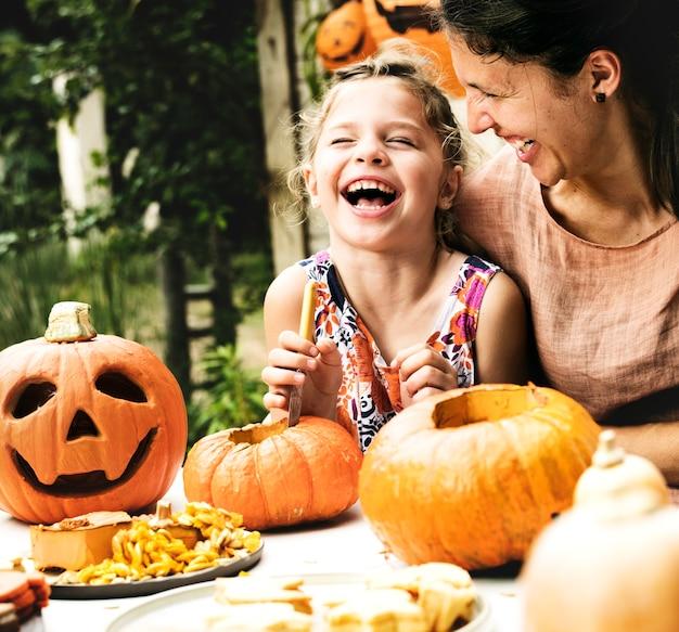 Jonge vrolijke meisjes snijdende pompoenen met haar mamma