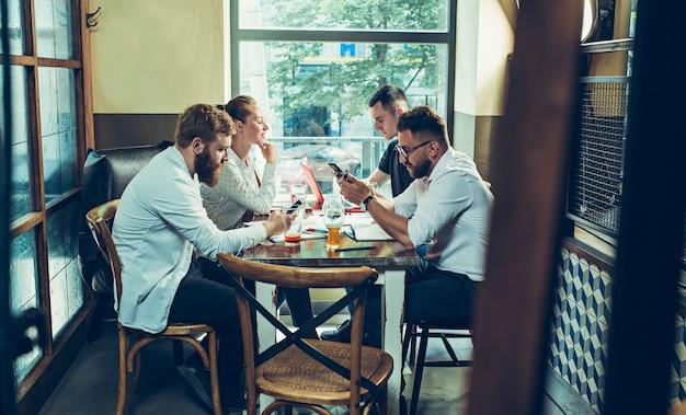 Jonge vrolijke mensen glimlachen en gebaar terwijl u ontspant in pub.