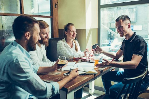 Jonge vrolijke mensen glimlachend en ontspannen in pub.