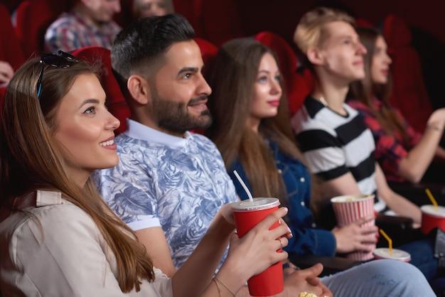 Jonge vrolijke mensen glimlachend vreugdevol ontspannen in de bioscoop kijken naar komedie film vrienden vriendschap entertainment activiteit vrije tijd plezier positiviteit levensstijl.