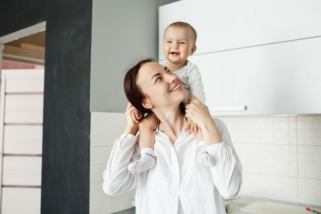 Jonge vrolijke moeder die haar baby op schouders draagt en lacht