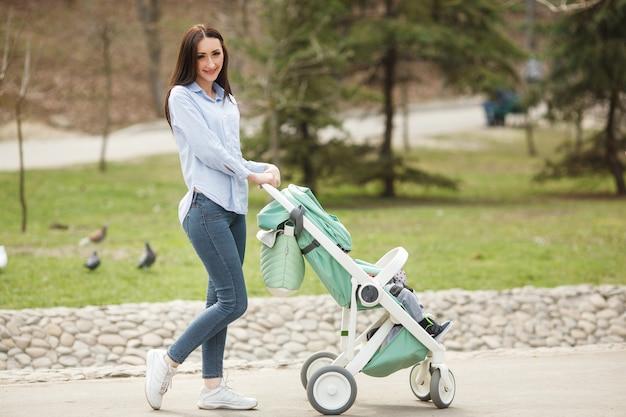 Jonge vrolijke moeder die met haar kind in carriege loopt