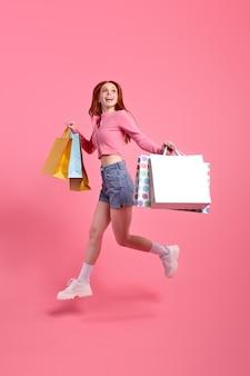 Jonge vrolijke mooie grappige funky dame die pakketten vasthoudt, geniet van het winkelen, gekleed in lichtgekleurd ...