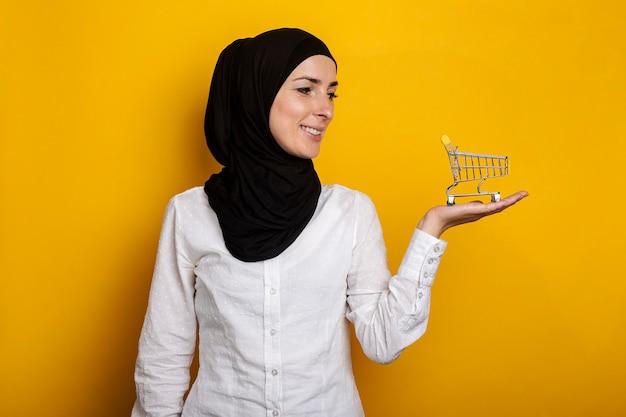 Jonge vrolijke moslimvrouw in hijab met een winkelwagentje op een geel