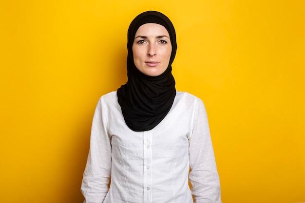 Jonge vrolijke moslimvrouw in hijab op een geel