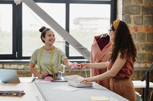 Jonge vrolijke naaister met meetlint passeren van haar collega stuk roze doek over tafel om nieuwe schoudervullingen te maken