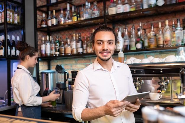 Jonge vrolijke ober met touchpad die zich voor camera bevindt tijdens het doorzoeken van online bestellingen per werkplek