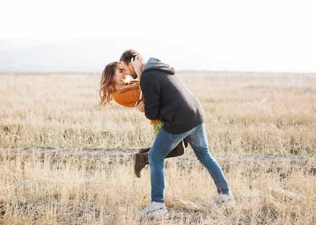 Jonge vrolijke paar man en vrouw buiten in een veld, knuffelen en dansen.