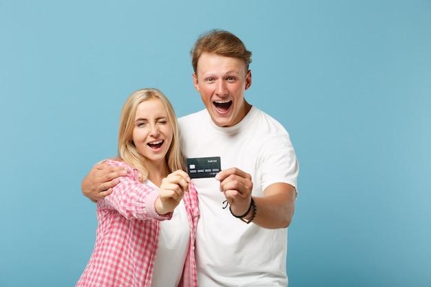 Jonge vrolijke paar twee vrienden man en vrouw in wit roze lege lege t-shirts poseren