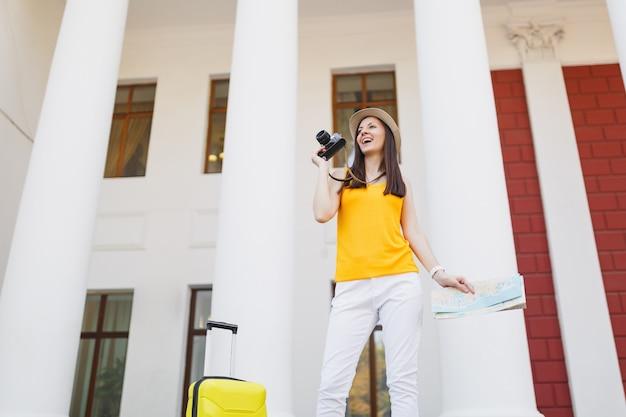 Jonge vrolijke reiziger toeristische vrouw in casual kleding met koffer, stadsplattegrond foto's maken op retro vintage fotocamera buiten. meisje op weekendje weg naar het buitenland. toeristische reis levensstijl.