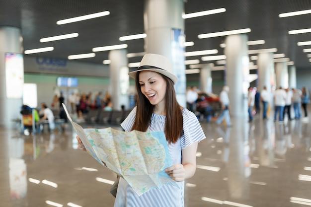 Jonge, vrolijke reiziger-toeristische vrouw in hoed met papieren kaart, zoekend naar route tijdens het wachten in de lobby op de internationale luchthaven