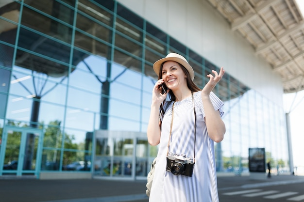 Jonge vrolijke reiziger toeristische vrouw met retro vintage fotocamera praten over mobiele telefoongesprekken vriend