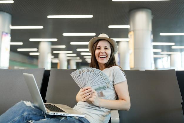 Jonge, vrolijke reizigerstoeristenvrouw die aan laptop werkt, houdt een bundel dollars vast in de lobby op de internationale luchthaven