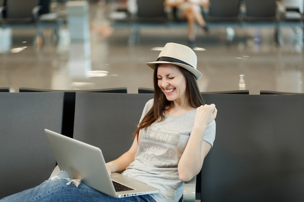 Jonge vrolijke reizigerstoeristenvrouw die aan laptop werkt, winnaargebaar doet, wachtend in de lobby op de internationale luchthaven