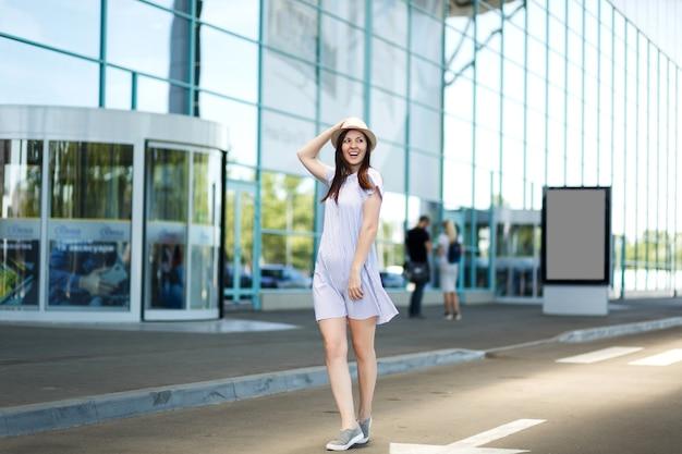 Jonge vrolijke reizigerstoeristenvrouw in hoed en lichte kleren die zich bij internationale luchthaven bevinden
