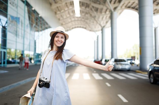 Jonge vrolijke reizigerstoeristenvrouw in hoed met retro vintage fotocamera met papieren kaart, vangt taxi op internationale luchthaven