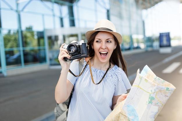 Jonge vrolijke reizigerstoeristenvrouw in hoed met retro vintage fotocamera, papieren kaart op internationale luchthaven