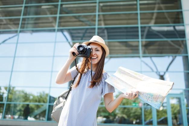Jonge vrolijke reizigerstoeristenvrouw maakt foto's op retro vintage fotocamera met papieren kaart op internationale luchthaven