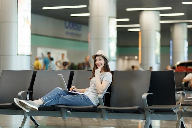 Jonge vrolijke reizigerstoeristenvrouw met hoed die aan laptop werkt terwijl ze wacht in de lobby op de internationale luchthaven