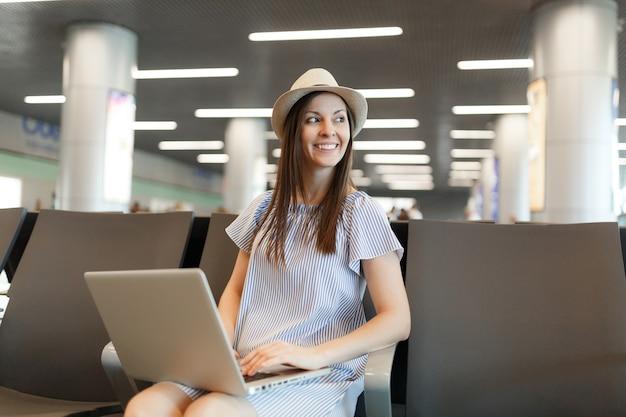 Jonge vrolijke reizigerstoeristenvrouw met hoed die op laptop werkt, opzij kijkend terwijl ze wacht in de lobbyhal op de internationale luchthaven