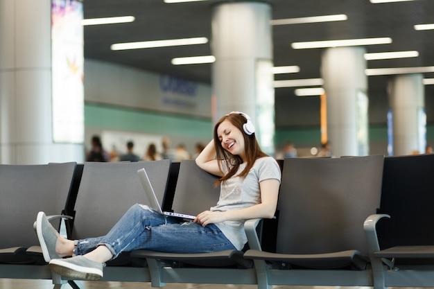 Jonge vrolijke reizigerstoeristenvrouw met koptelefoon die muziek luistert die op laptop werkt, wacht in de lobby op de internationale luchthaven
