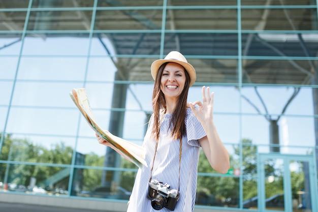 Jonge, vrolijke reizigerstoeristenvrouw met retro vintage fotocamera houdt papieren kaart vast, toont ok gebaar op internationale luchthaven