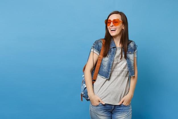 Jonge vrolijke schattige vrouw student met rugzak dragen oranje hart bril opzij kijken hand in hand in zakken geïsoleerd op blauwe achtergrond. onderwijs op de middelbare school. kopieer ruimte voor advertentie.