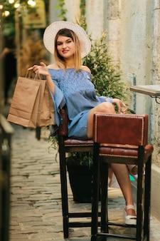 Jonge vrolijke shopaholic vrouw zitten in straat café met papieren boodschappentassen