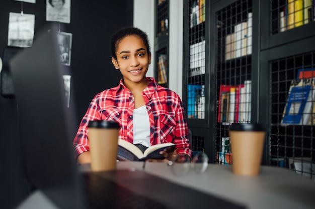Jonge vrolijke student zit aan de universiteitsbibliotheek tijdens de koffiepauze van studeren