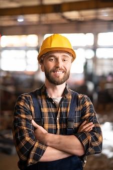 Jonge vrolijke succesvolle ingenieur of voorman in werkkleding en beschermende helm staande in de werkplaats