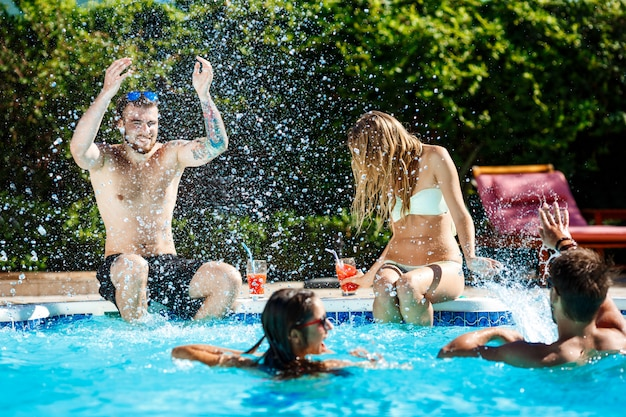 Jonge vrolijke vrienden glimlachen, lachen, ontspannen, zwemmen in het zwembad