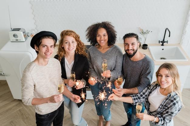 Jonge vrolijke vrienden met fluiten champagne en sprankelende bengaalse lichten die naar je kijken terwijl je in de keuken staat