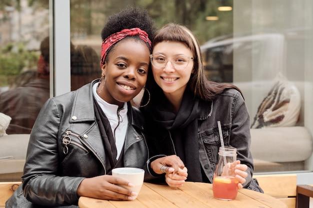 Jonge vrolijke vriendinnen in vrijetijdskleding die naar je kijken met een brede glimlach