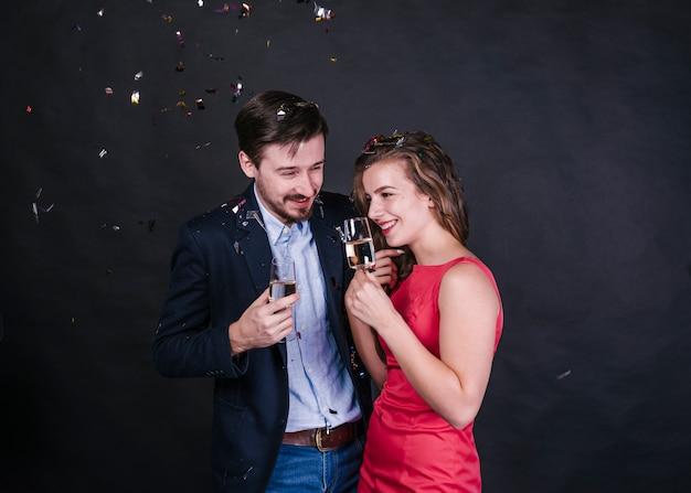 Jonge vrolijke vrouw dichtbij de mens met glazen drank tussen het werpen van confettien