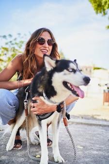 Jonge vrolijke vrouw die haar siberische husky aait voor in het park