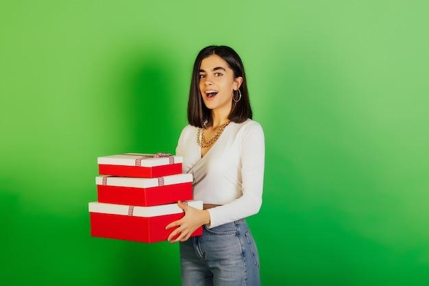 Jonge vrolijke vrouw die in vrijetijdskleding rood-witte giftdozen op groene oppervlakte houdt.