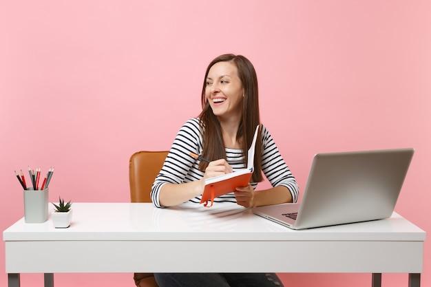 Jonge, vrolijke vrouw die opzij kijkt en notities schrijft op een notebook die zit en werkt aan een wit bureau met een moderne pc-laptop