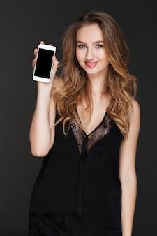 Jonge vrolijke vrouw die telefoonvertoning toont aan camera.
