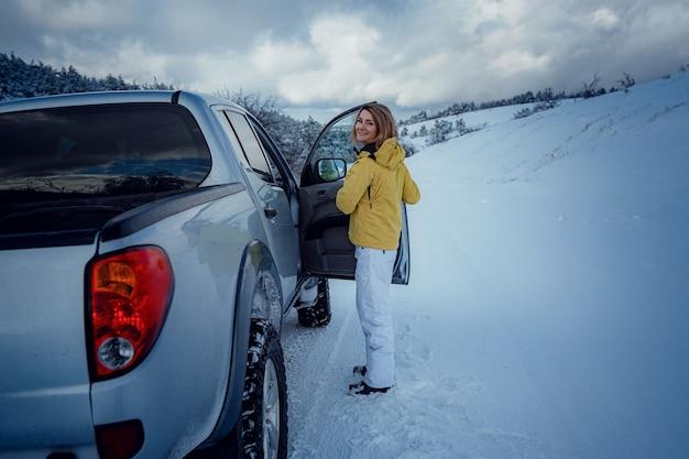Jonge vrolijke vrouw die zich voordeed tegen de auto en het sneeuwbos. aantrekkelijke vrouw gekleed in gele jas zittend op passagiersstoel in zilveren auto, winterseizoen