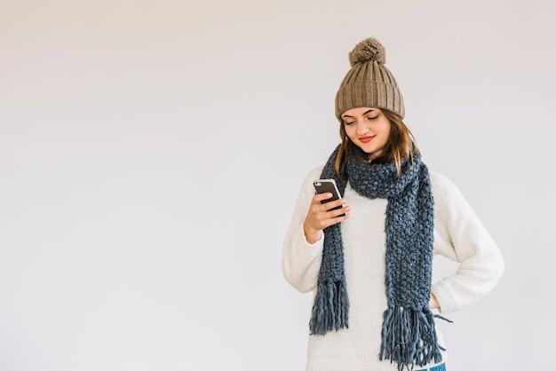 Jonge vrolijke vrouw in hoed en sjaal met smartphone