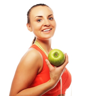 Jonge vrolijke vrouw in sportkleding met appel, geïsoleerd op witte achtergrond