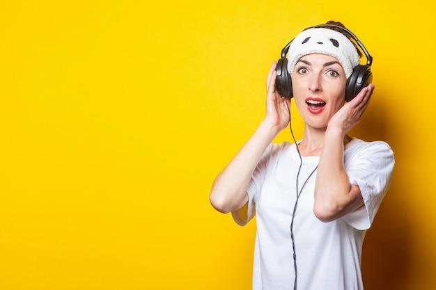 Jonge vrolijke vrouw luistert naar muziek op koptelefoon.