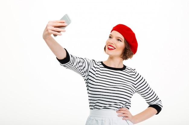 Jonge vrolijke vrouw maakt selfie via de mobiele telefoon.