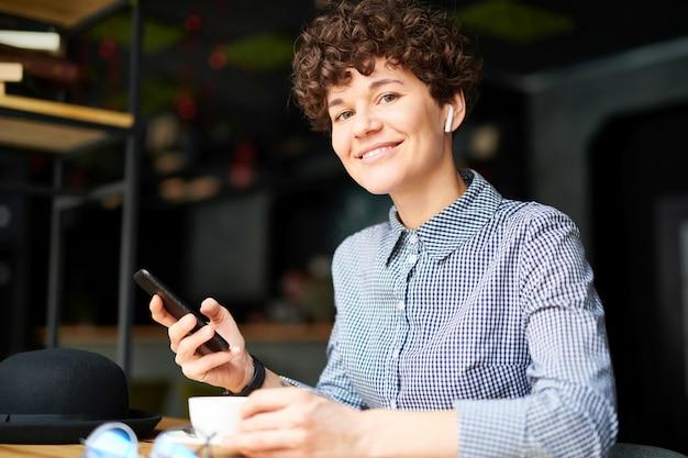 Jonge vrolijke vrouw met airpods en smartphone op zoek naar jou terwijl u ontspant met muziek in café