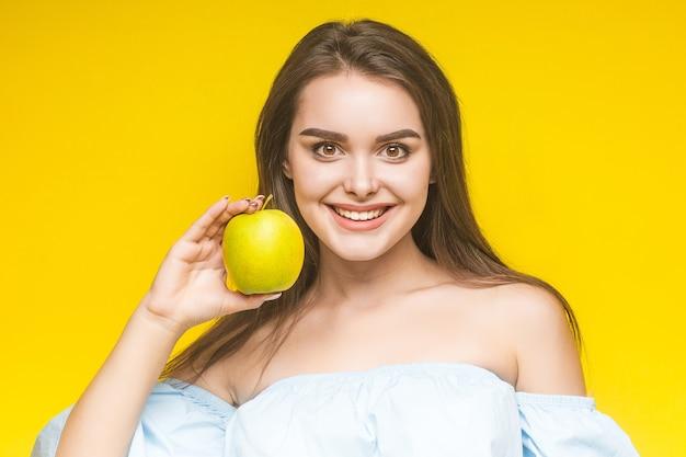 Jonge vrolijke vrouw met appel, geïsoleerd op geel.