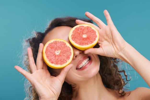 Jonge vrolijke vrouw met gezonde tanden en huid die plakjes verse, sappige grapefruit vasthoudt met haar ogen op blauw geïsoleerd Premium Foto