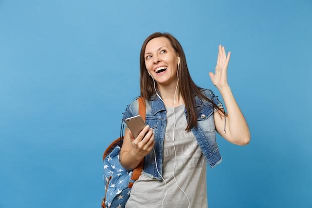 Jonge vrolijke vrouw student in denim kleding met rugzak, koptelefoon verspreiden handen luisteren muziek houden mobiele telefoon geïsoleerd op blauwe achtergrond. onderwijs op de universiteit. kopieer ruimte voor advertentie.