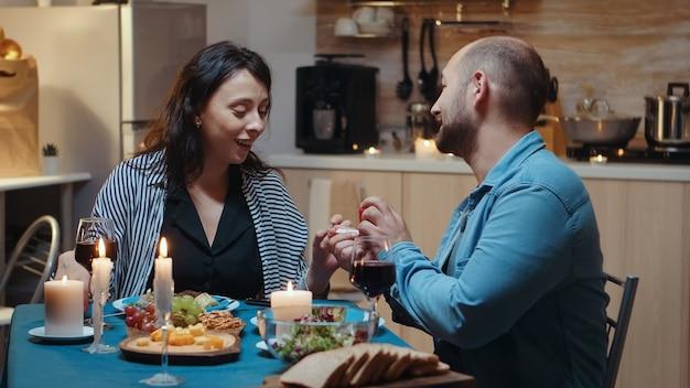 Jonge vrolijke vrouw wordt verrast door huwelijksaanzoek van haar man. man die een voorstel doet aan zijn vriendin in de keuken tijdens een romantisch diner. gelukkige blanke vrouw die lacht is sprakeloos Premium Foto